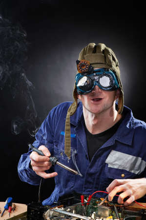 research scientist: Crazy funny genious with soldering iron Stock Photo