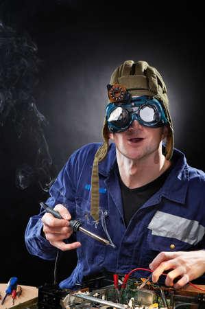 scienziati: Divertente pazzo genio con saldatore Archivio Fotografico