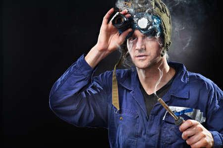 Crazy genius guy wearing weird hat with soldering iron in hand