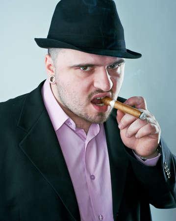 Macho man with cigar in black hat photo