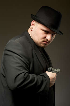 Dangerous man in black suite and hat with gun. photo