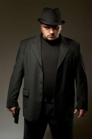 Hombre peligroso en conjunto negro y sombrero con pistola.