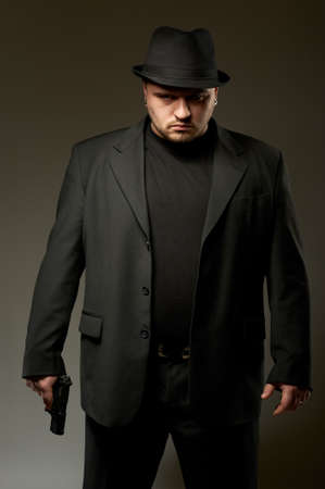 Dangerous man in black suite and hat with gun. Stock Photo - 9044783