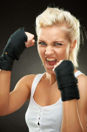 Agressive young beautiful blond boxer girl with bandages on hands, studio shot Stock Photo - 9156597