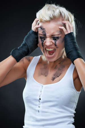 Emotional portrait of a beautiful screaming young punk woman with dirt on her face, studio shot photo