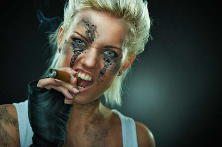Closeup portrait of a beautiful young caucasian punk woman with dirty face and cigar in her mouth