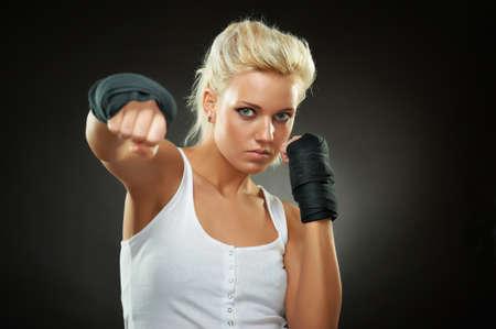 Portrait of a beautiful caucasian boxer girl with black bandage on hands, studio shot Standard-Bild