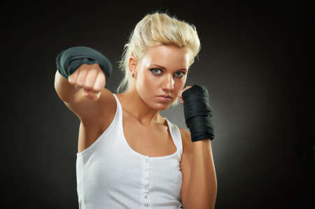 strong girl: Portrait of a beautiful caucasian boxer girl with black bandage on hands, studio shot Stock Photo