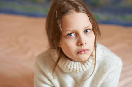 Portrait of a sad blond little girl, shallow DOF photo