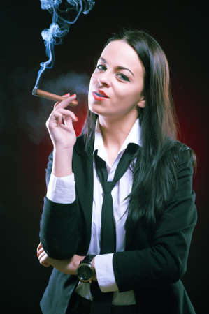Beautiful elegant young woman with cigar, studio shot