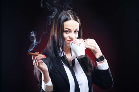 Beautiful elegant young woman with cigar and cup of coffee, studio shot