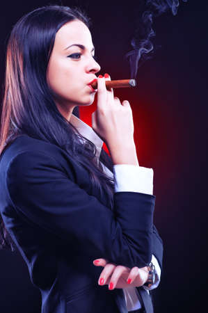 Beautiful elegant young woman with cigar, studio shot photo