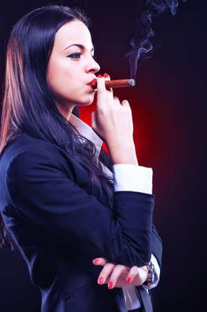 Beautiful elegant young woman with cigar, studio shot photo