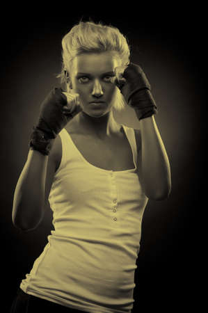 Attractive blonde fighter girl, studio shot, sepia Stock Photo - 9306033