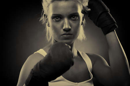 Attractive blonde fighter girl, studio shot, sepia photo