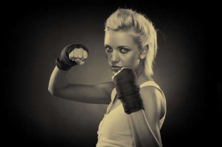 Attractive blonde fighter girl, studio shot, sepia Stock Photo - 9306012