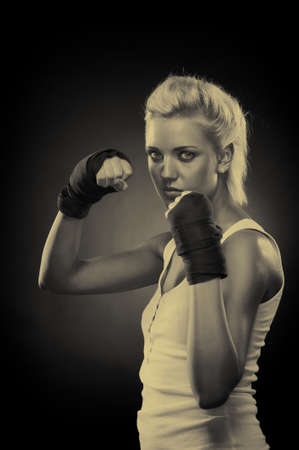 Attractive blonde fighter girl, studio shot, sepia Stock Photo - 9306024