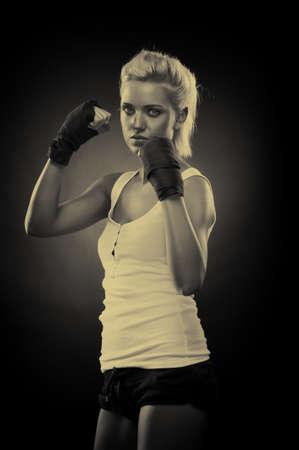 Attractive blonde fighter girl, studio shot, sepia Stock Photo