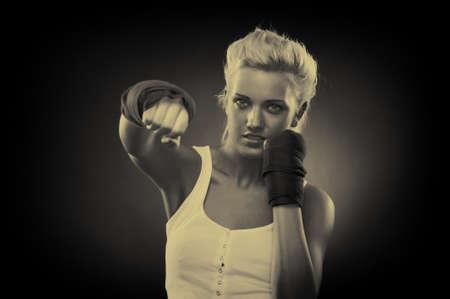 Attractive blonde fighter girl, studio shot, sepia Stock Photo - 9306008