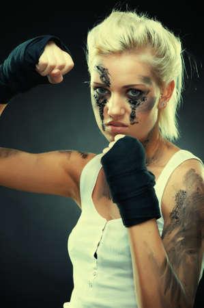 Attractive blonde fighter girl, studio shot, cross processed