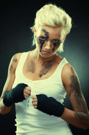 Attractive blonde fighter girl, studio shot, cross processed photo