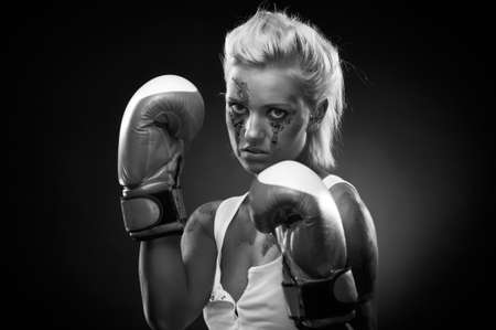 Attractive blonde fighter girl, studio shot, black and white photo