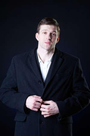 Studio dark portrait of a handsome stylish young man in coat