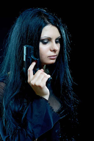beautiful goth girl with gun on black photo