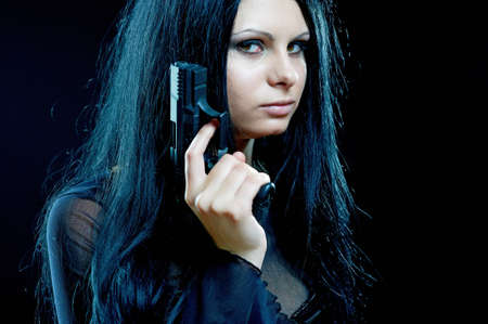 woman with gun: beautiful goth girl with gun on black Stock Photo