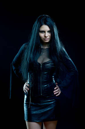 Attractive goth girl standing on black photo