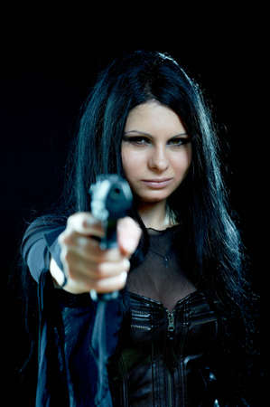 beautiful goth girl with gun on black focus on face photo