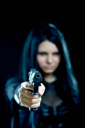 beautiful goth girl with gun on black focus on gun