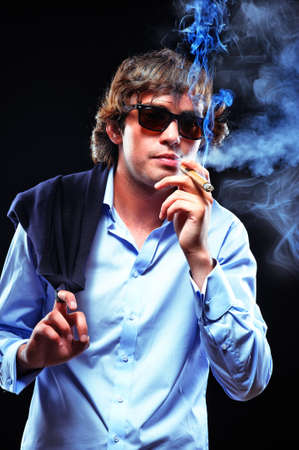 Portrait of a smoking man in sunglasses photo