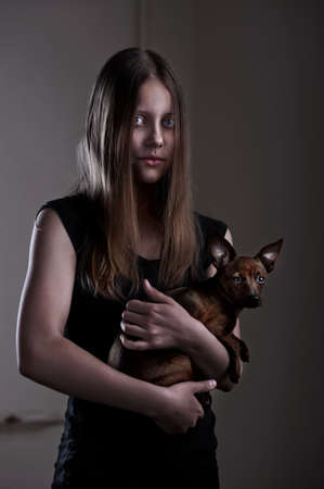 Portrait of a beautiful evil teen girl with little doggy photo