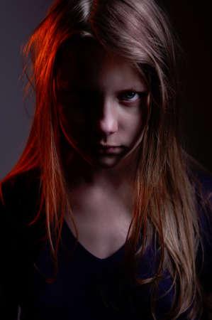 Closeup portrait of a scary little demon girl, studio shot photo