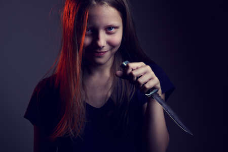 Portrait of a scary demonic teen girl with a knife photo