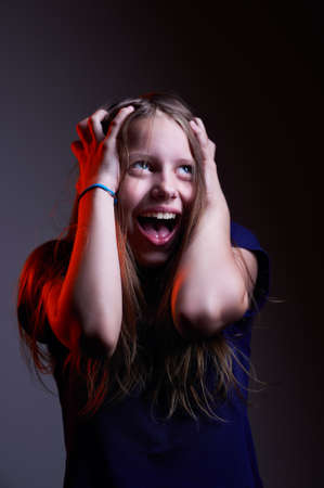 Portrait of unhappy screaming teen girl, studio shot photo