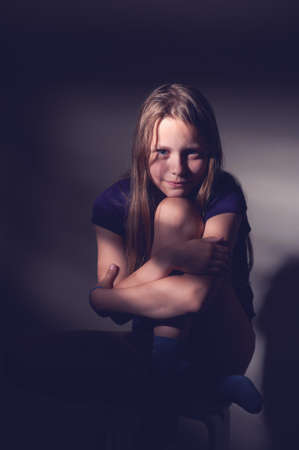 contrasty: Portrait of a teen smiling girl sitting on a chair in a dark room, contrasty light from window