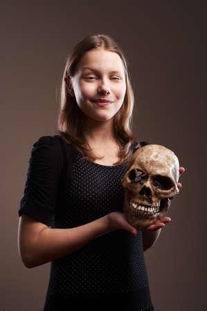 Smiling teen girl holding skull