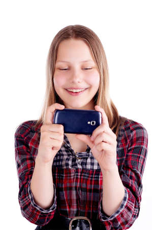 Happy teen girl laughing and use mobile phone, studio shot photo