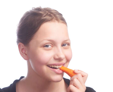 Teen girl eating carrot, studio shot photo