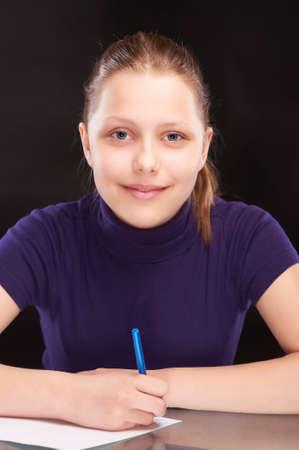 Smart teen girl writng something Standard-Bild