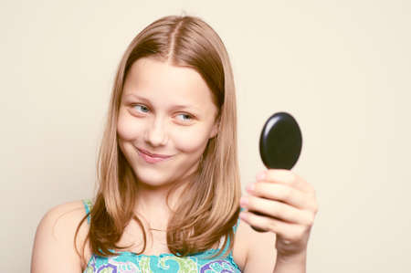 attractiveness: Happy teen girl looking at the mirror and making funny faces Stock Photo