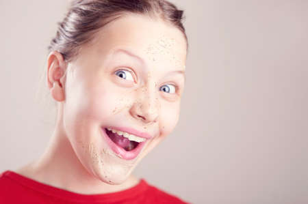 mack: Happy teen girl with scrub mack on her face having fun and making funny faces Stock Photo