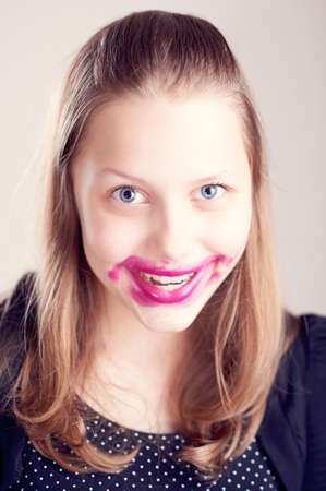 Happy teen girl making funny faces with pomade on lips and cheeks photo