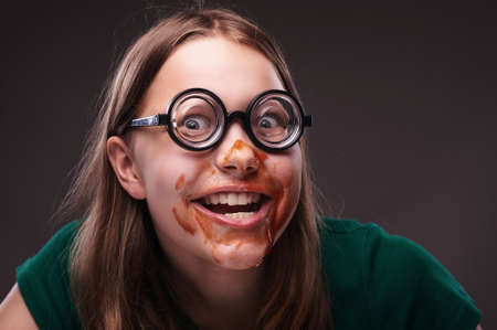 nerd girl: Crazy nerd girl in eyeglasses with ketchup or blood on her face Stock Photo