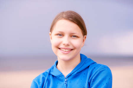 gir: Cute happy teen gir staying on the beach and smiling Stock Photo