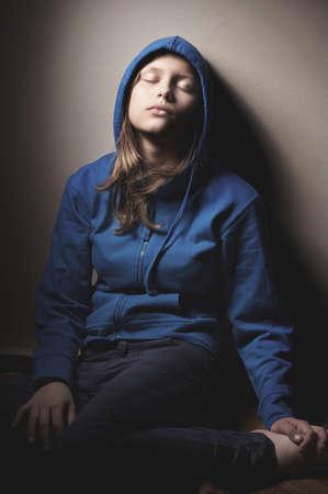 closed eyes: Droevig tienermeisje in kap zitten met gesloten ogen Stockfoto