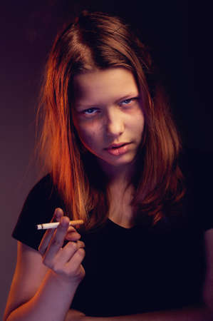 Depressed teen girl with cigarette smoking photo