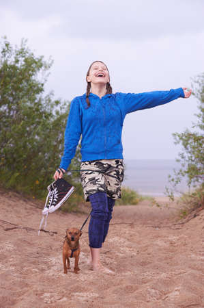 Happy teen girl standing on the beach with her dog and enjoy the rain photo